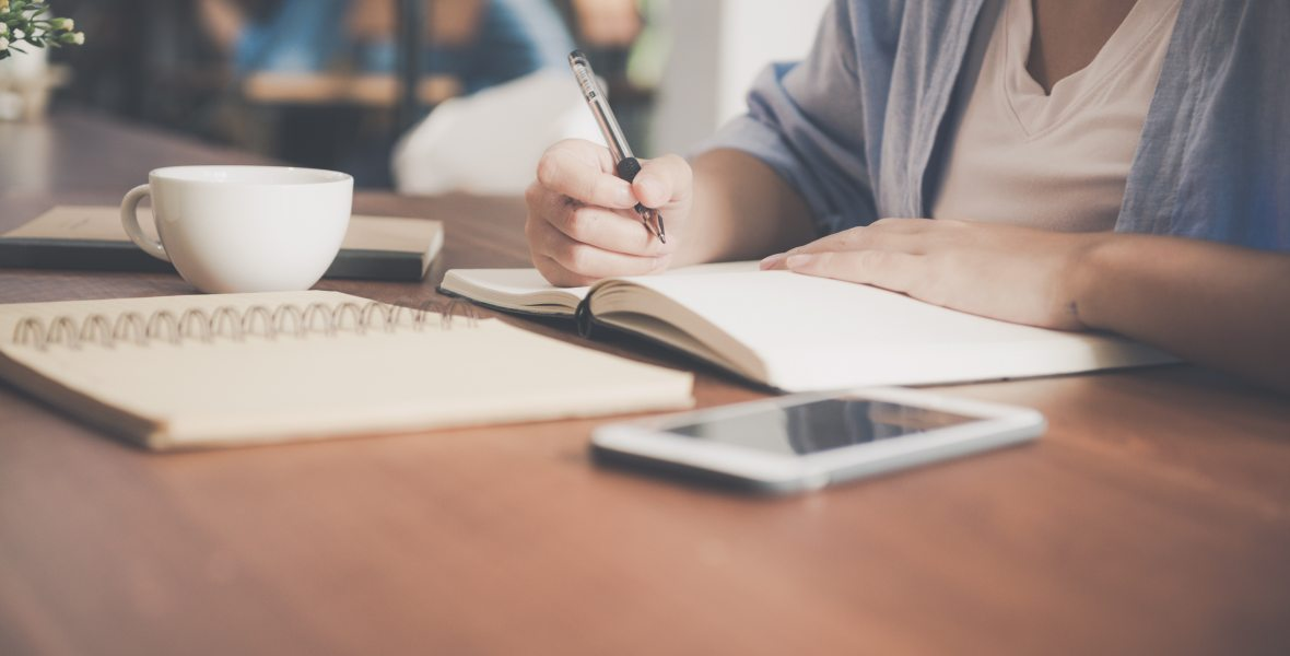ID: Woman at desk (with a cell phone, and a cup of tea) writing in a notebook.