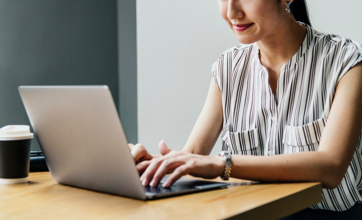 Woman typing on laptop on a wooden desk, with a coffee.